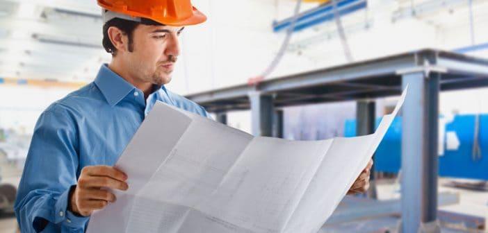 פועל בניין מסתכל על שרטוט בנייה